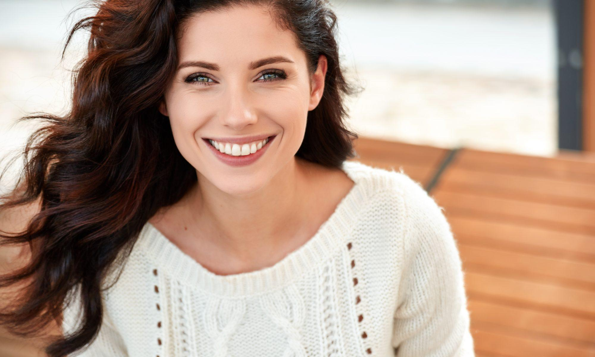 Woman with straight teeth and cream jumper